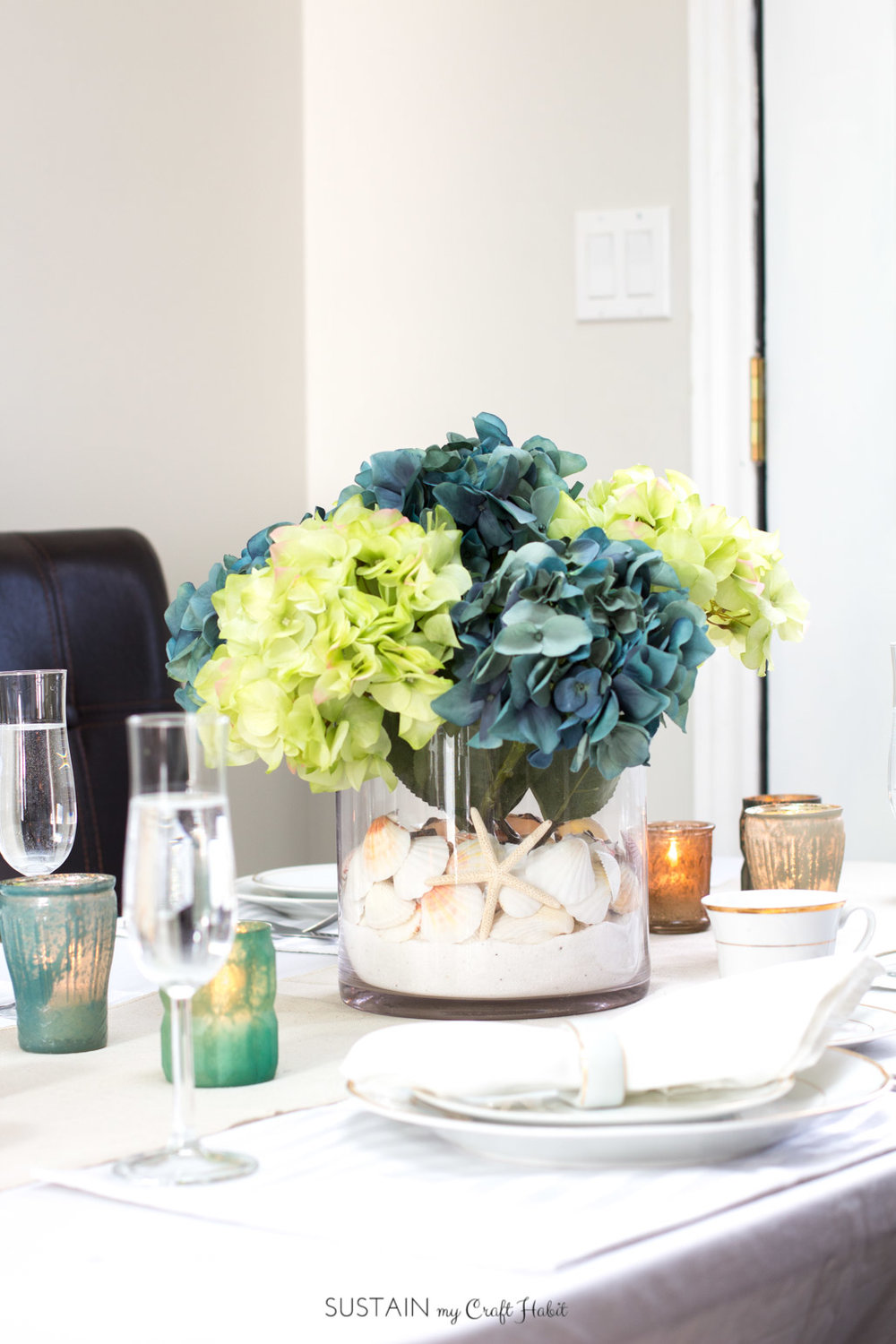 Stunning! Learn how to create an elegant beach theme centerpiece to accent this gorgeous summer tablescape. The perfect DIY idea for a destination wedding, coastal bridal shower or beachy party. Video tutorial included. #afloral #sponsored