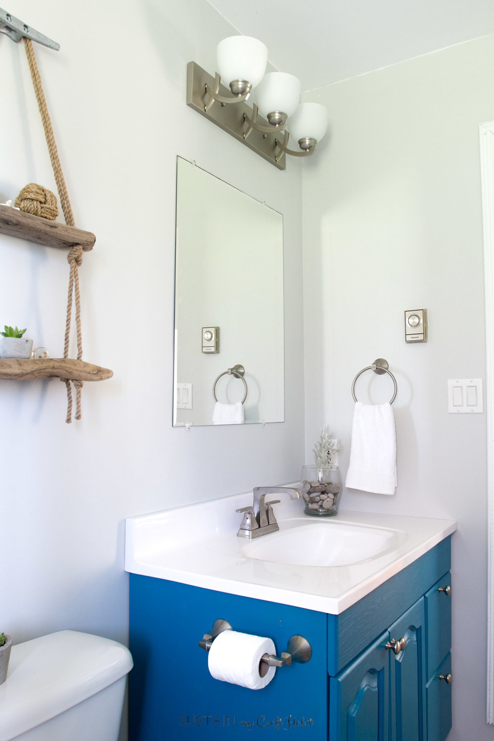 Love this teal pop of colour in this gorgeous small beach theme bathroom remodel. So many fun DIY ideas to give a room that relaxing coastal vibe.