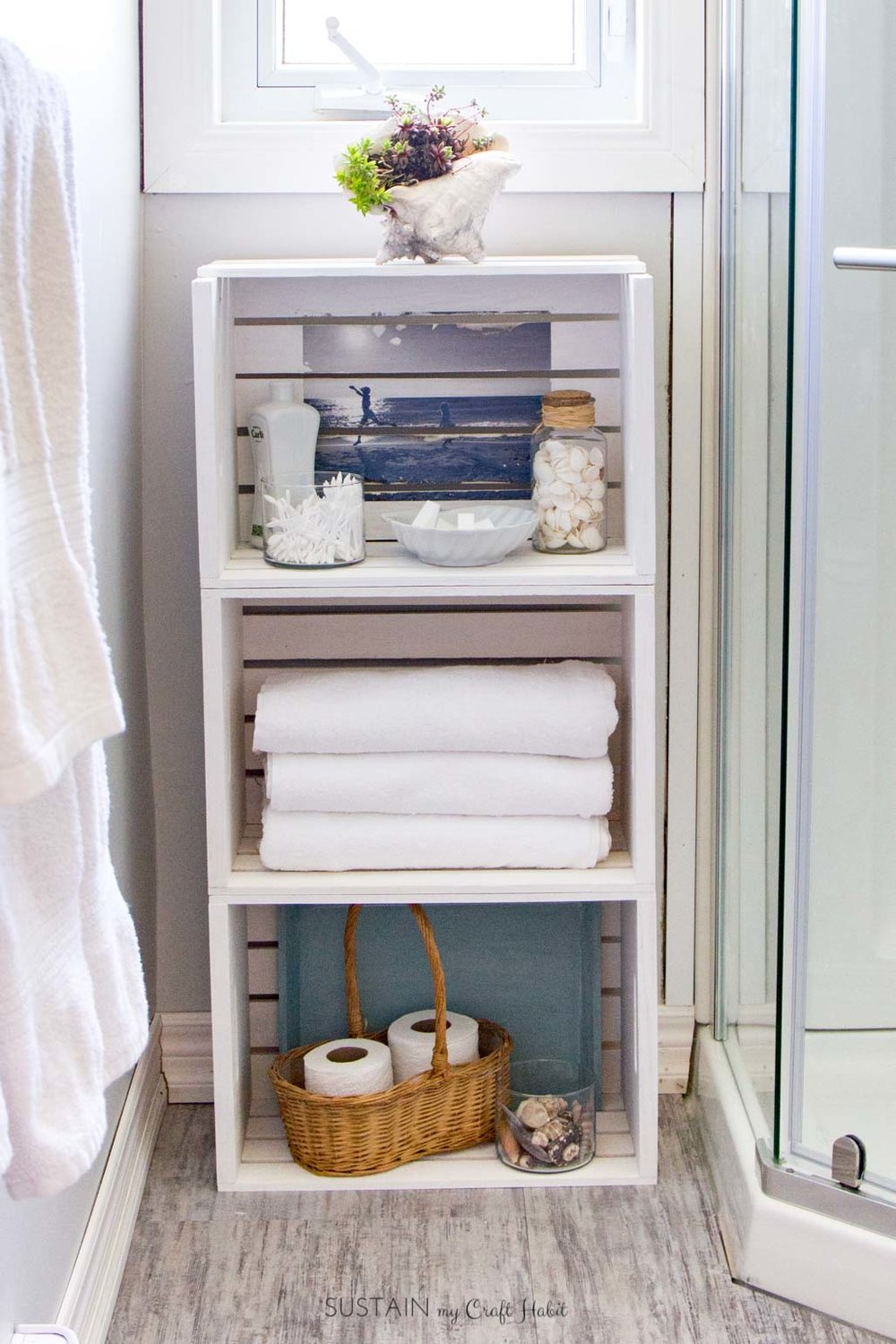 Such a great DIY storage idea for all those bathroom essentials! Just one idea in a whole beach themed bathroom makeover. Click to see the complete small bathroom remodel reveal!