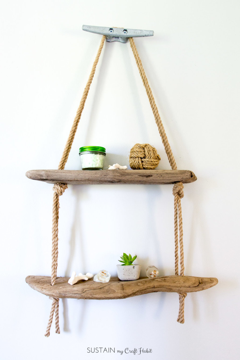 Such a fun idea to make for a beach themed bathroom or coastal style cottage. Use some driftwood, rope and an anvil to make this simple bathroom display idea.