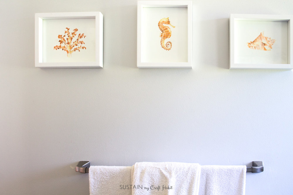 Ocean-inspired watercolor art as a part of a complete beach themed bathroom makeover. Includes other creative DIY ideas for a coastal style bathroom makeover.