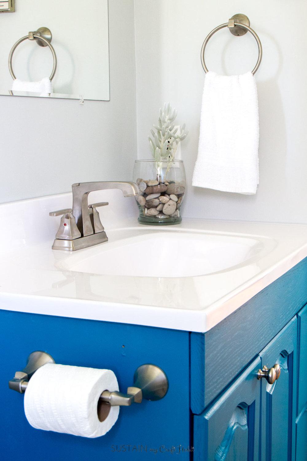 These fixtures from Delta Faucet Canada's Ashlyn Collection are perfect in this coastal style small bathroom remodel. Click through for more beach theme bathroom DIY ideas! [sponsored]