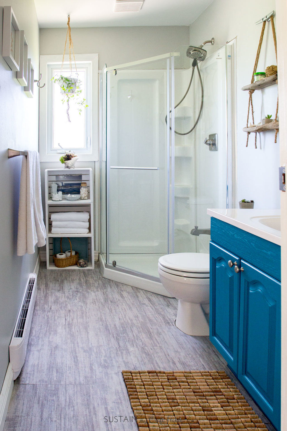 Can't get over the transformation of this small bathroom into a beach themed bathroom retreat! So many simple and budget-friendly bathroom makeover DIY ideas!