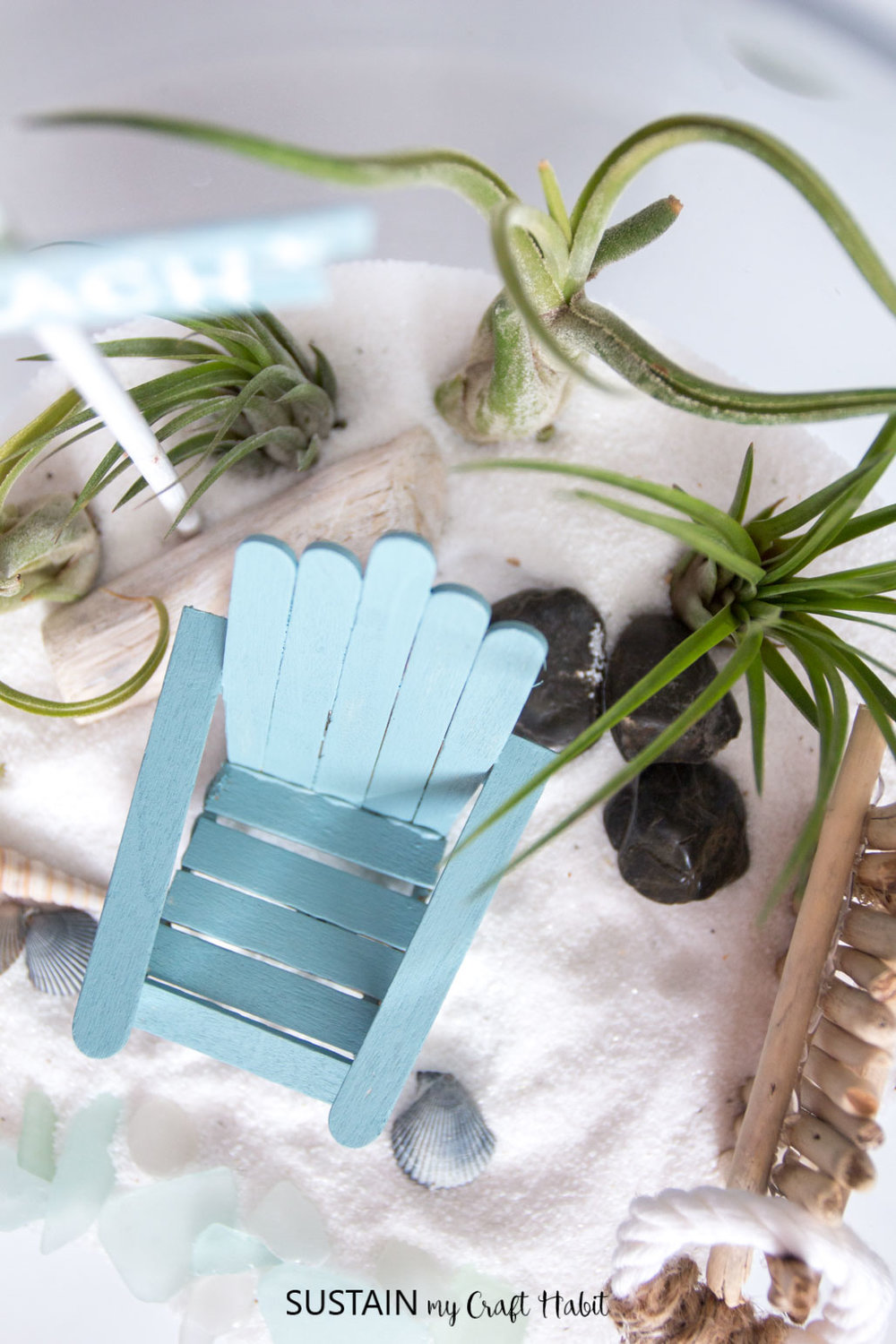 DIY Muskoka chair made with wooden craft sticks as a part of a beachy air plant mini-garden. Simple Popsicle stick craft idea!