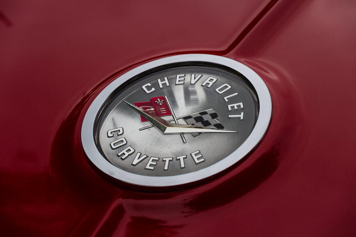 The familiar emblem on a  late 1960's bright red Corvette Stingray
