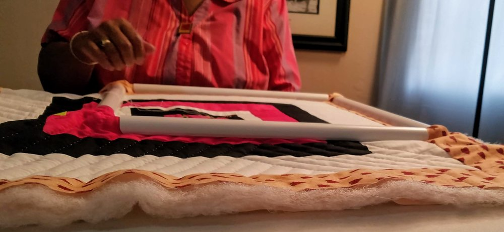 Mary Ann Pettway hand quilting one of her original compositions.