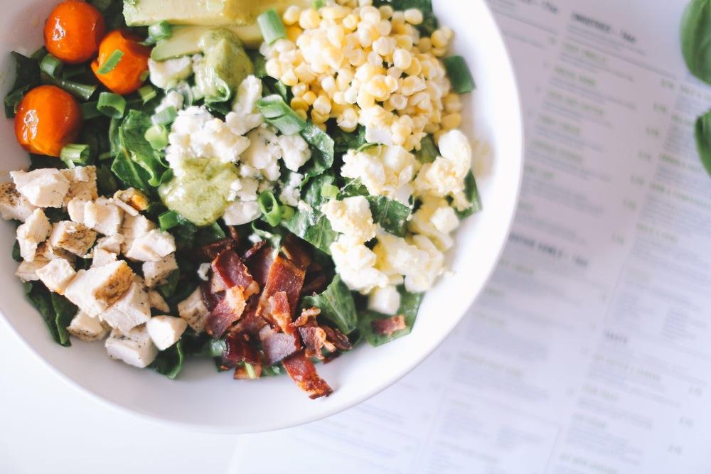 VILLAGE COBB: organic romaine ~ chicken ~ bacon ~ organic tomato ~ avocado ~ organic egg ~ onion ~ crumbled cheese ~ raw organic corn   ||  dressing: avo-goddess OR village ranch  ||  11.95