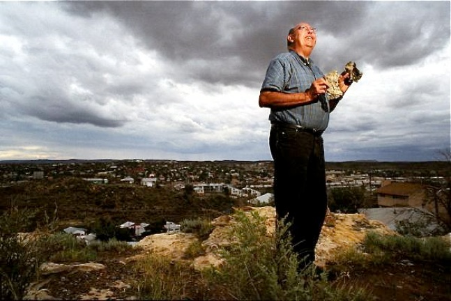I am Chuck Wade, and I live in Gallup, New Mexico. This is a photo of me with Gallup in the background. I am holding some UFO crash debris that I retrieved from a site on the Plains of San Augustin in southern New Mexico. Photo courtesy Craig Robinson