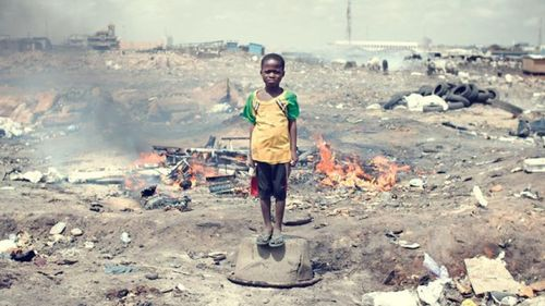 A child stands in the middle of a landfill in ghana