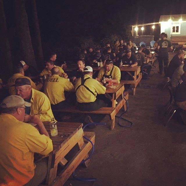 """First responders resting and eating a hot meal at Thunder Island Brewing 24 hours after the fire started"""