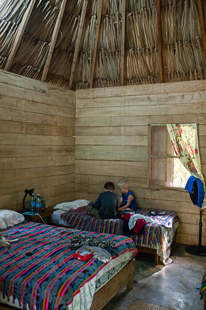 The boys relax inside our hut, which had cool concrete floors, thatched roof, fans, and an attached bathroom/shower with hot water.