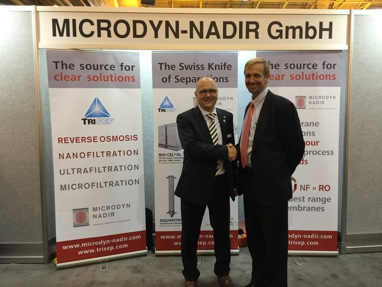 WALTER LAMPARTER, CEO OF MICRODYN-NADIR, AND PETER KNAPPE, PRESIDENT OF TRISEP, SHAKE HANDS AT WEFTEC AFTER ANNOUNCING THE SALE OF TRISEP CORPORATION TO MICRODYN-NADIR.