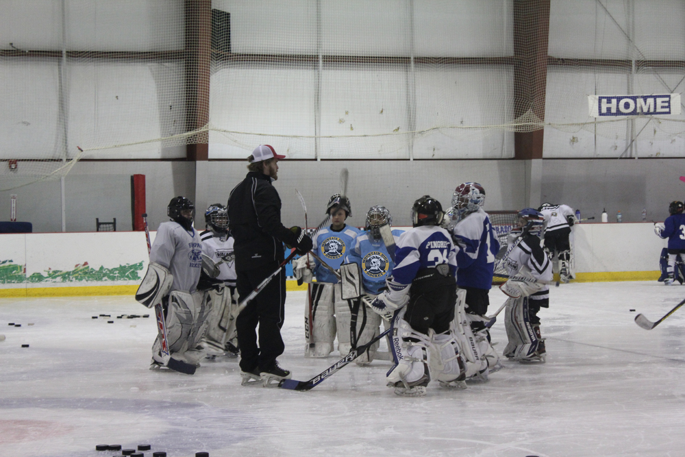 MHH and Denver University Pioneers goalie coach Joe Howe discussing the game plan with the goalies in our Mite and Squirt Group