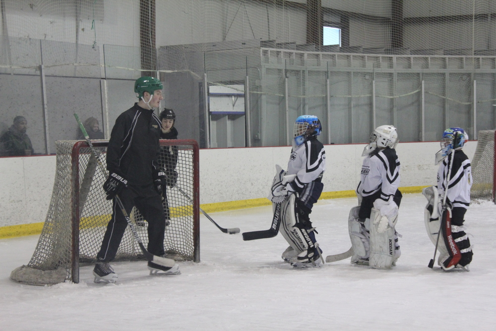 Coach Maiszon Balboa has the attention of the goalies as he explains situations when the puck is behind the net.