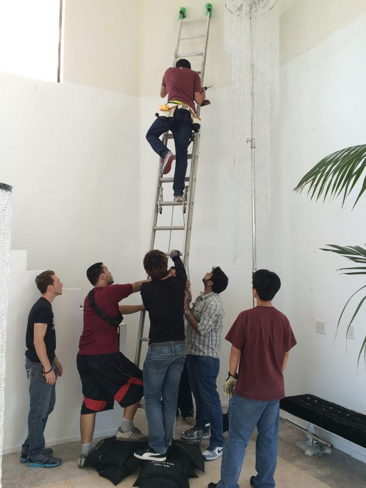 PD, Eduardo Bautista, sets up on of the lamps with the help of the crew