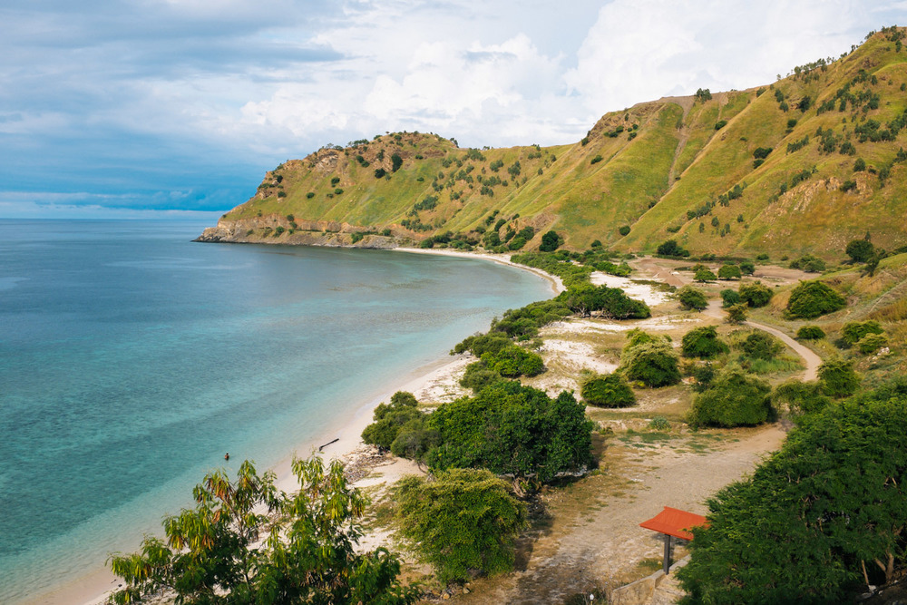 An unspoiled beach surrounded by green mountains in Dili