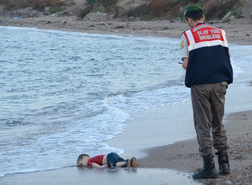 A Turkish police officer stands near of the drowned Syrian boy, 2015 @Reuters