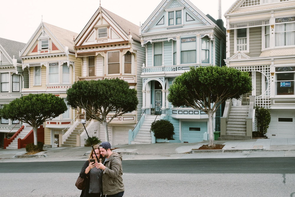 "Tourists posing for a selfie in front of the ""Painted Ladies"", one of the most visited sites in SF"