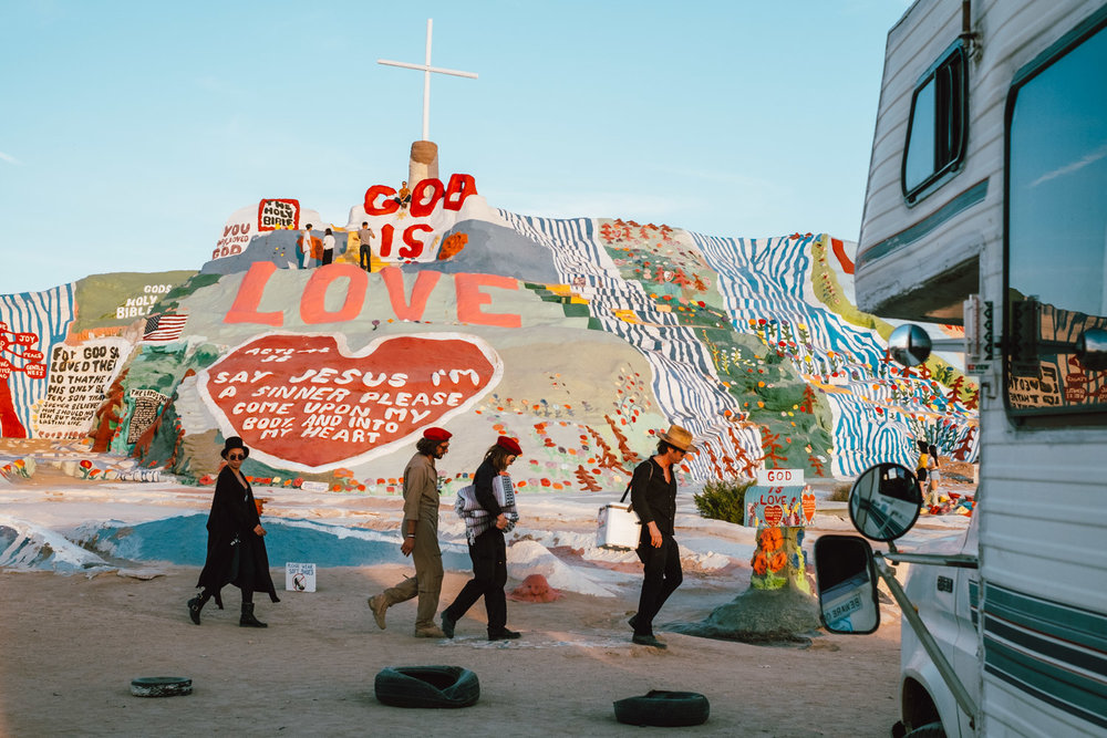 A troupe of gypsies walking by Salvation Mountain, CA