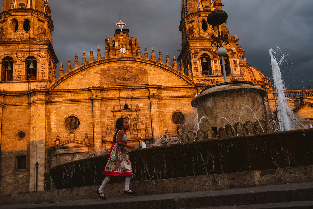 A girl playing around a fountain in Guadalajara, Mexico.