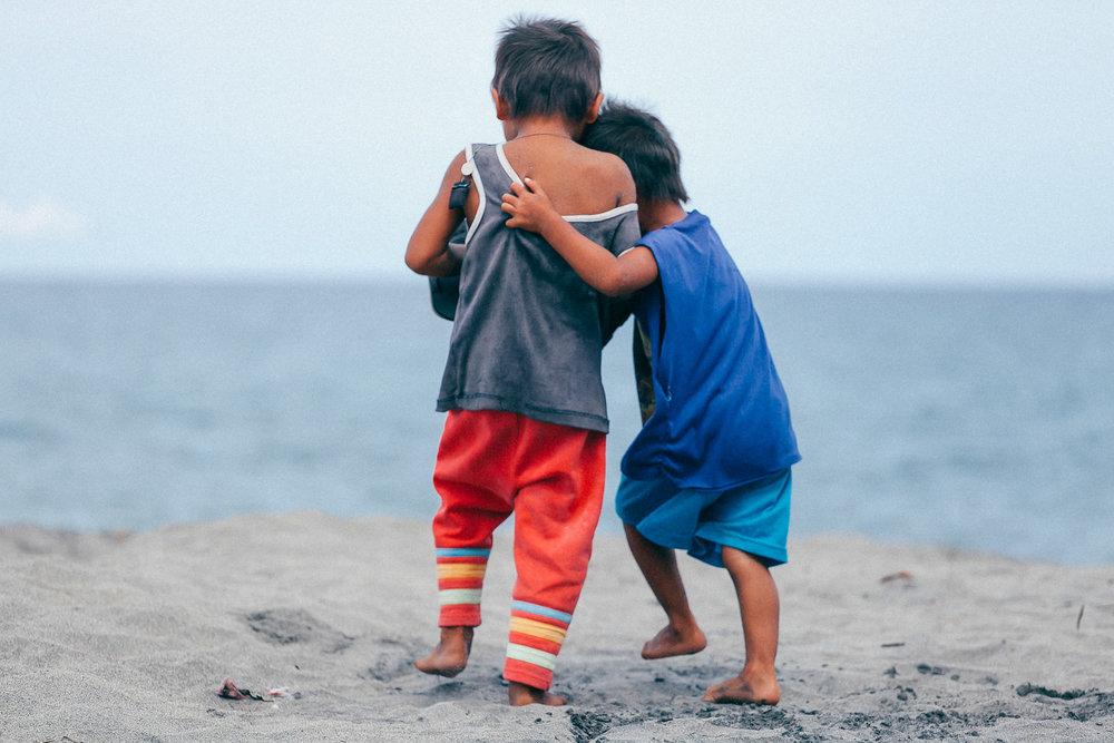 Crianças brincam na praia em Tacloban, Filipinas.