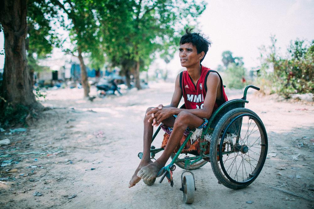 Mouen posa para uma foto em frente ao local onde mora, aos arredores de um lixão afora de Phnom Penh.
