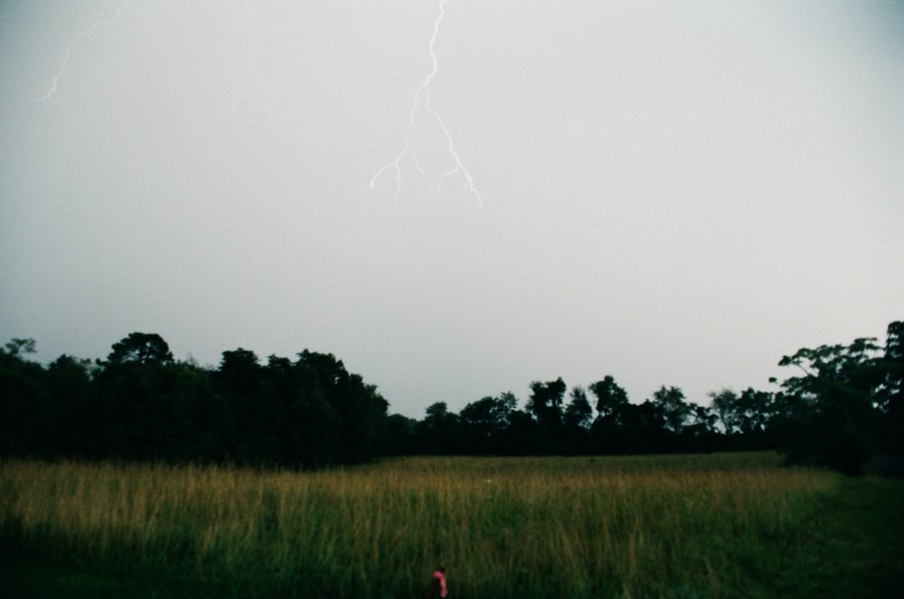 Faint lightning bolts over field on Kodak Portra 400