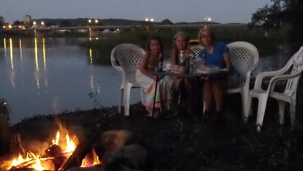 A campfire by river edge is magical.