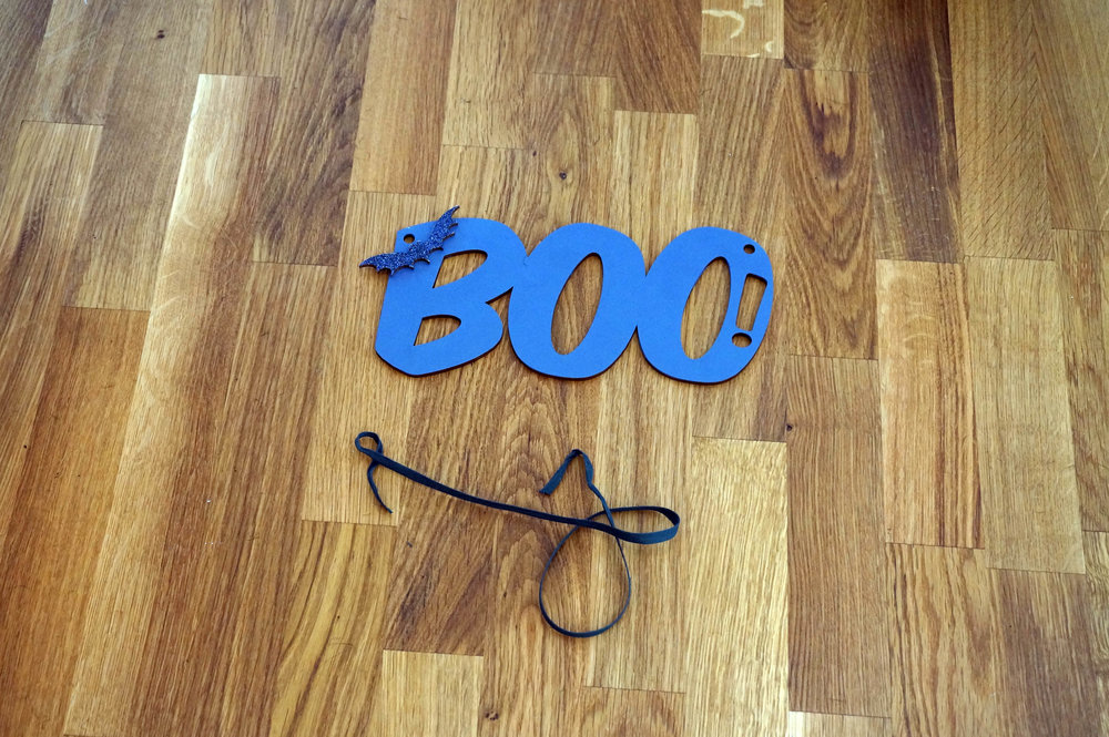 Remove the quarter inch tight weave Italian ribbon from East Grove's BOO! Hanging Sign.