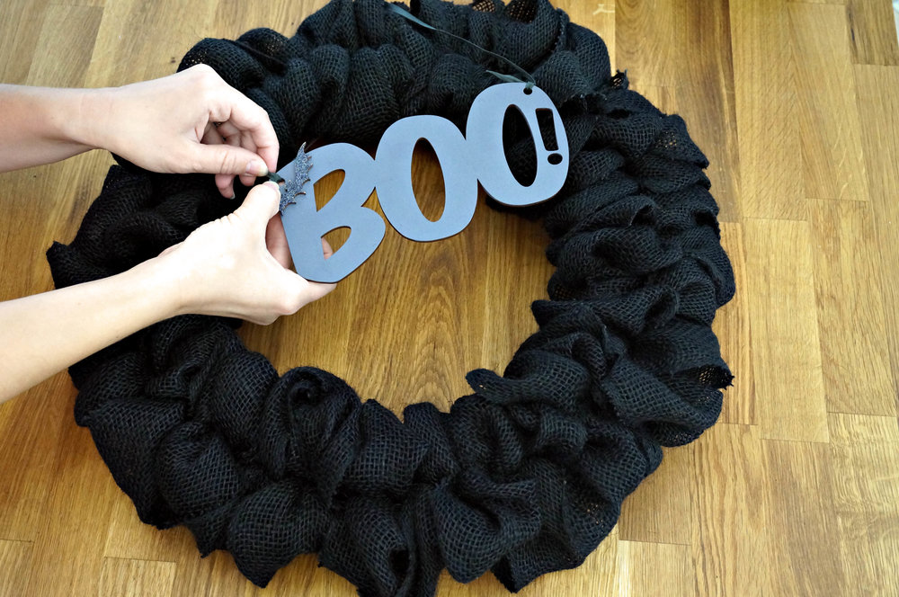 There are two ways to attach the BOO! sign. The first would to hang the sign around the wreath so that BOO! hangings in the wreath opening.