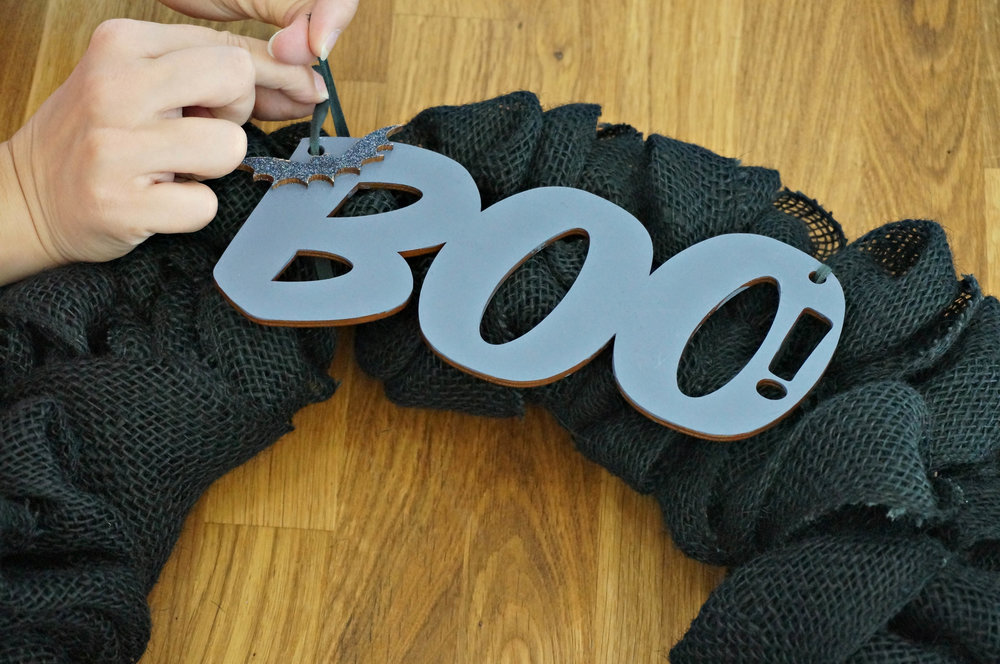 Tie each of the two pieces of ribbon around the wreath, attaching the BOO! sign.