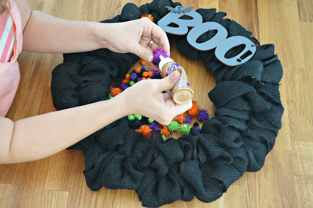 Use your tacky glue (or hot glue) to attach the little puffs (or other decorations) to the wreath.