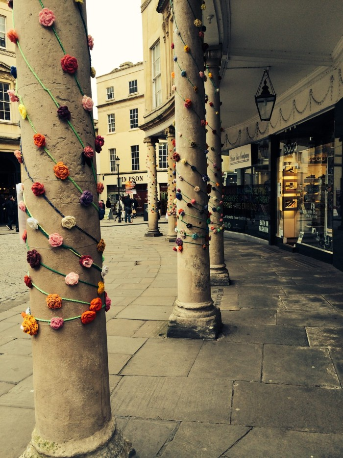 Rose Yarn bomb. Detail of crochet roses around colonnades in Bath Uk