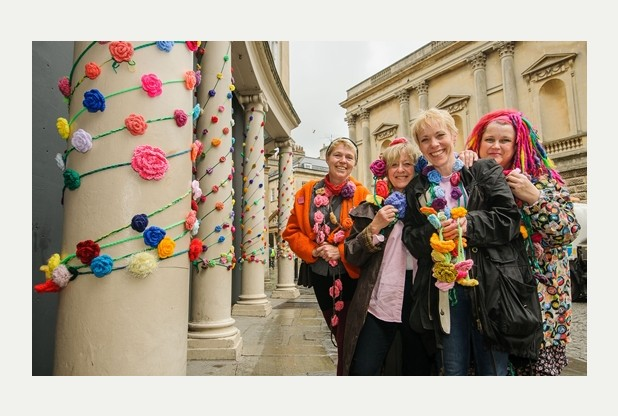 Crochet roses wrapped around colonnades as part of the Yarnbomb for Bath In Fashion 2014