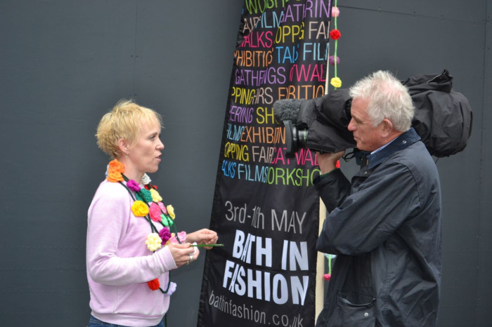 Crochet and mosaic artist Emma Leith talking to the press about the crochet rose yarn bomb