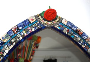 Close up of ceramic rose incorporated into a mosaic mirror frame