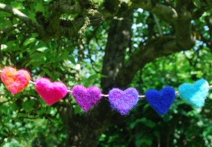 colourful needle felted hearts hanging 'bunting style' in a tree