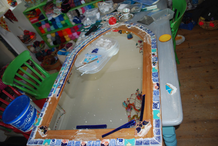Large mirror on a table in the process of being mosaiced using china plates