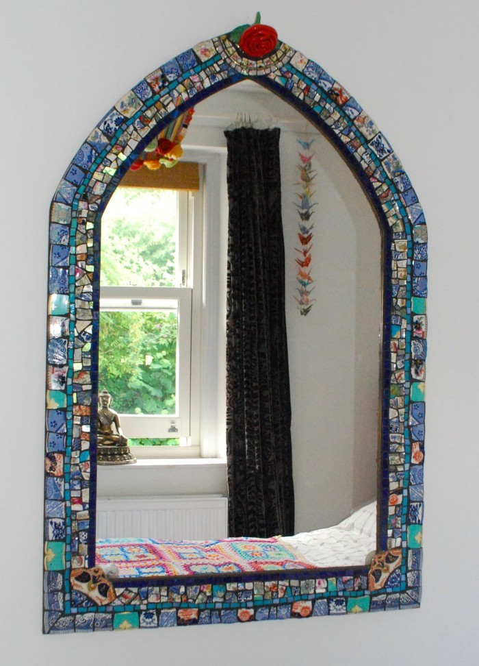 Mosaic Mirror hanging on a wall with a crochet blanket and a statue of Buddha reflected in mirror