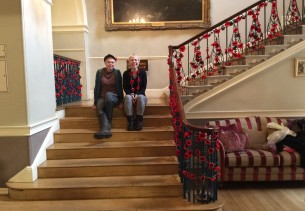 Two ladies sat on the stairs at Bath Guildhall surrounded by Crochet poppies