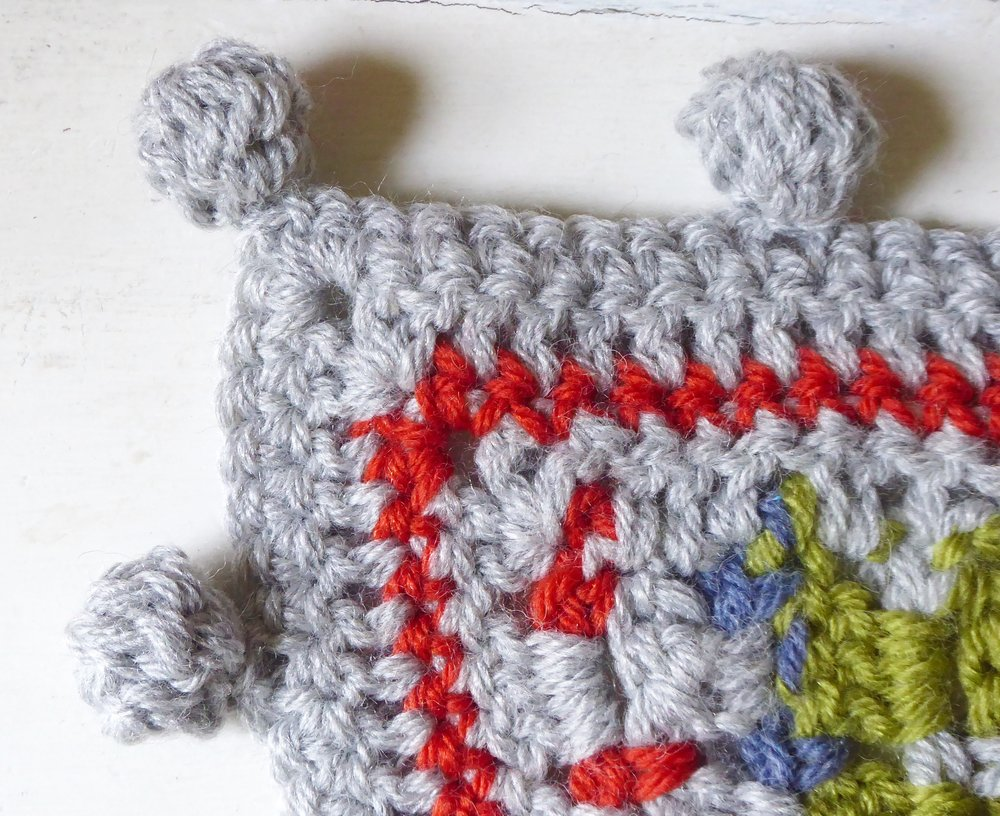Corner detail of pompom bobble edging in crochet lap blanket by Emma Leith
