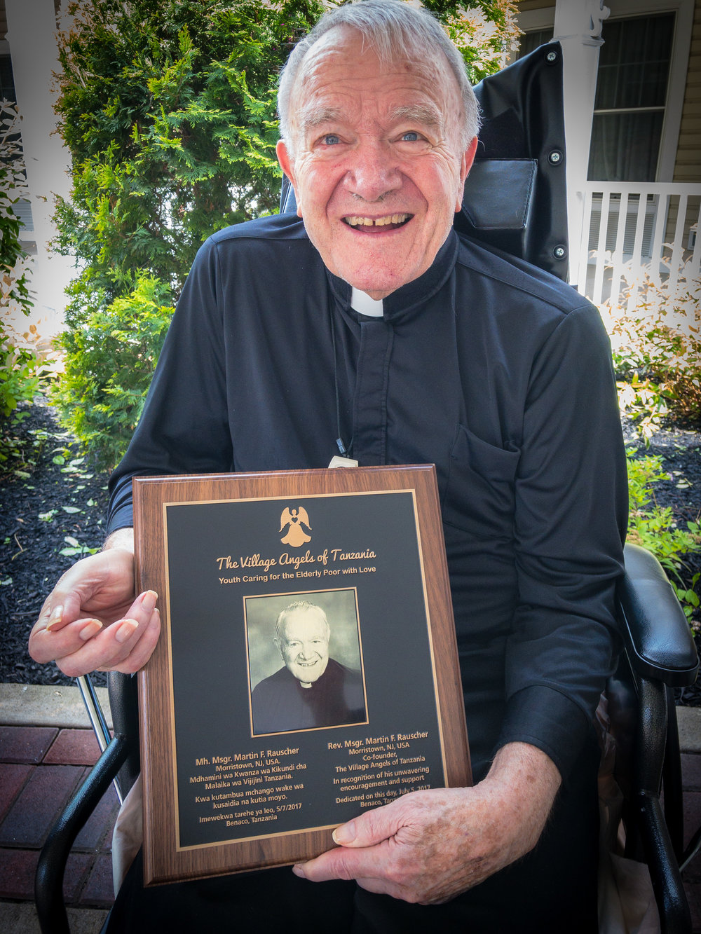 Fr. Martin with the multipurpose room dedication plaque before it was brought to Tanzania