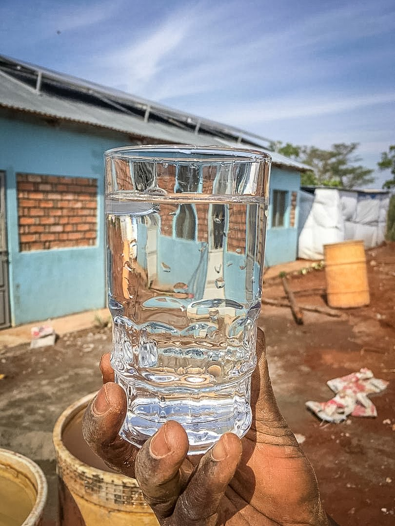 A glass of water from the well. A secondary storage tank will hold water for drinking, cooking, etc.