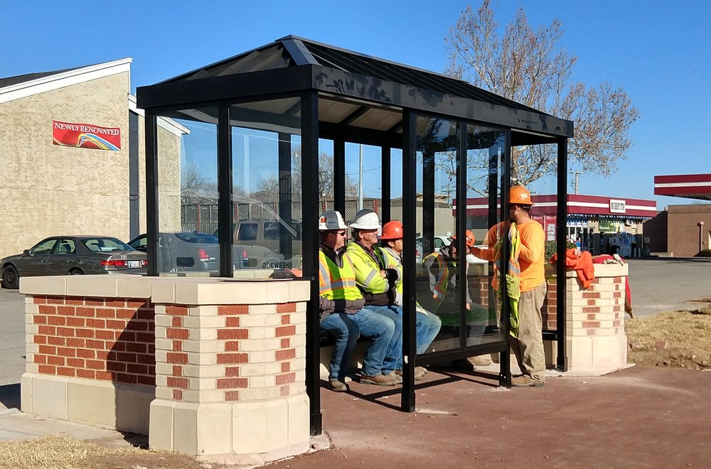 "Construction workers demonstrate one of the new enclosed bus shelters along Lindsey Street. The ""Cherokee Gothic"" theme was applied to the bridges, bus stops, and benches along the corridor, providing a unique gateway from the Interstate leading to the University of Oklahoma campus."