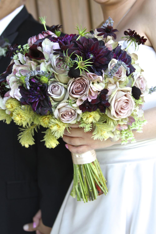 Burgandy and Bi-color Dahlias, Burgandy Scabiosa, Sahara and Amnesia Roses, Leucadendron, Lavender Springs, and Chocolate Cosmos.