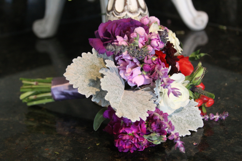 Red Piano Garden Roses, Purple Lisianthus, Lavender Springs, Magenta Stock, White Ranunculus, Red Hypericum Berries, and Dusty Miller.