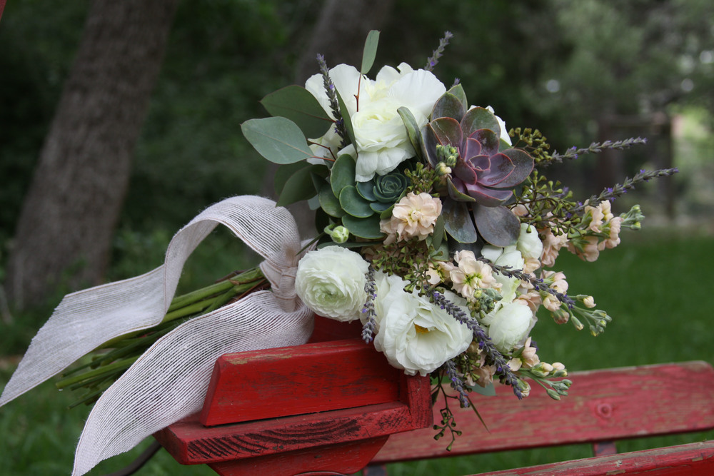 White Peonies, White Ranunculus, White Lisianthus, Peach Stock, Lavender Springs, Succulents, and Seeded Eucalyptus.