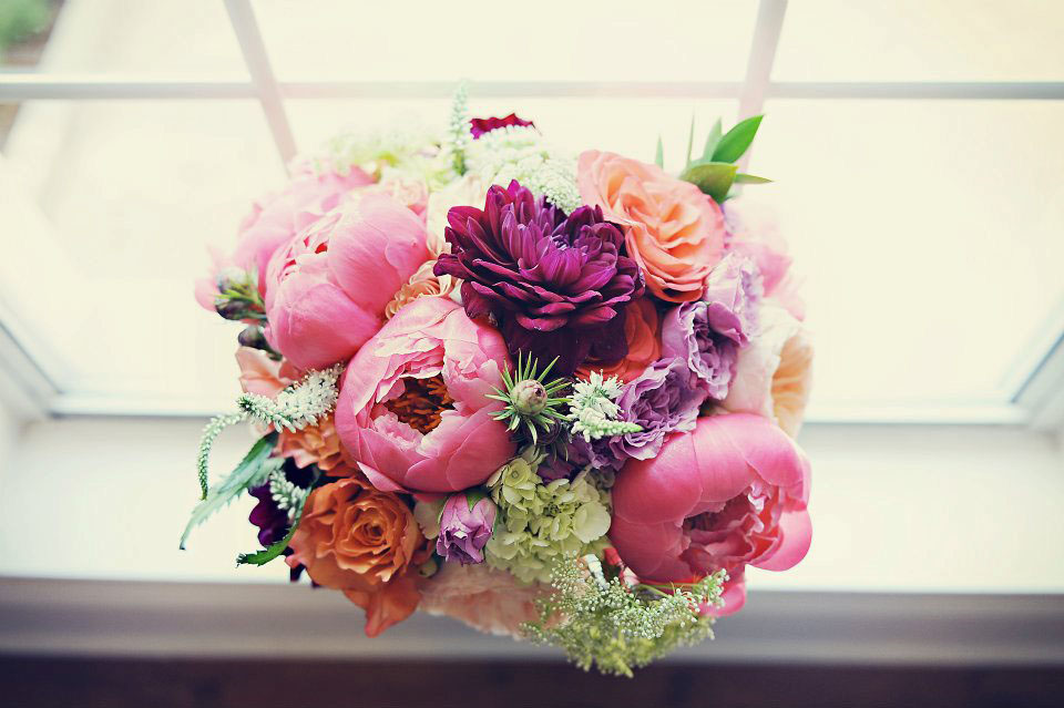 Coral Charm Peonies, Juliet Garden Roses, Free Spirit Roses, Magenta Dahlias, Little Silver Spray Roses, Lime Hydrangea, White Veronica, Leucadendron, and Queen Anne's Lace.