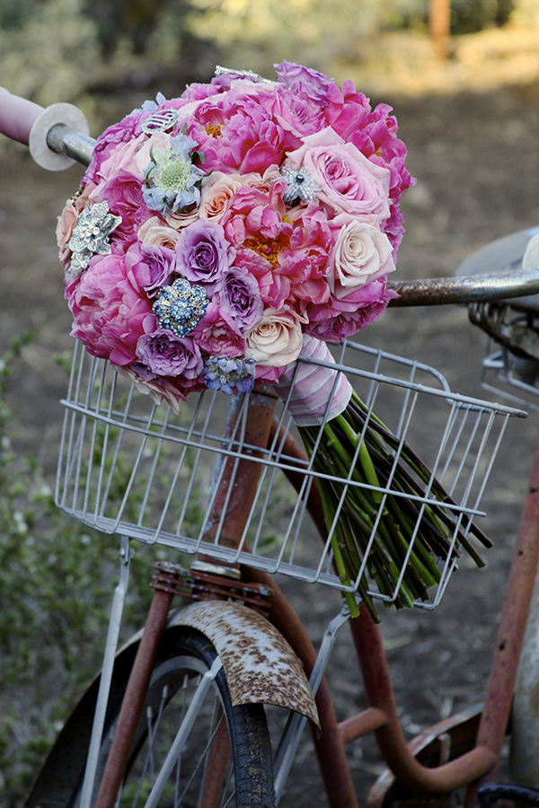 Pink Mink Proteas, Coral Charm Peonies, Darcy Garden Roses, Blue Moon Spray Roses, Free Spirit Roses, Porcelina and Ilse Spray Roses, Blue Scabiosa, Silver Brunia, Dusty Miller, and antique brooches.