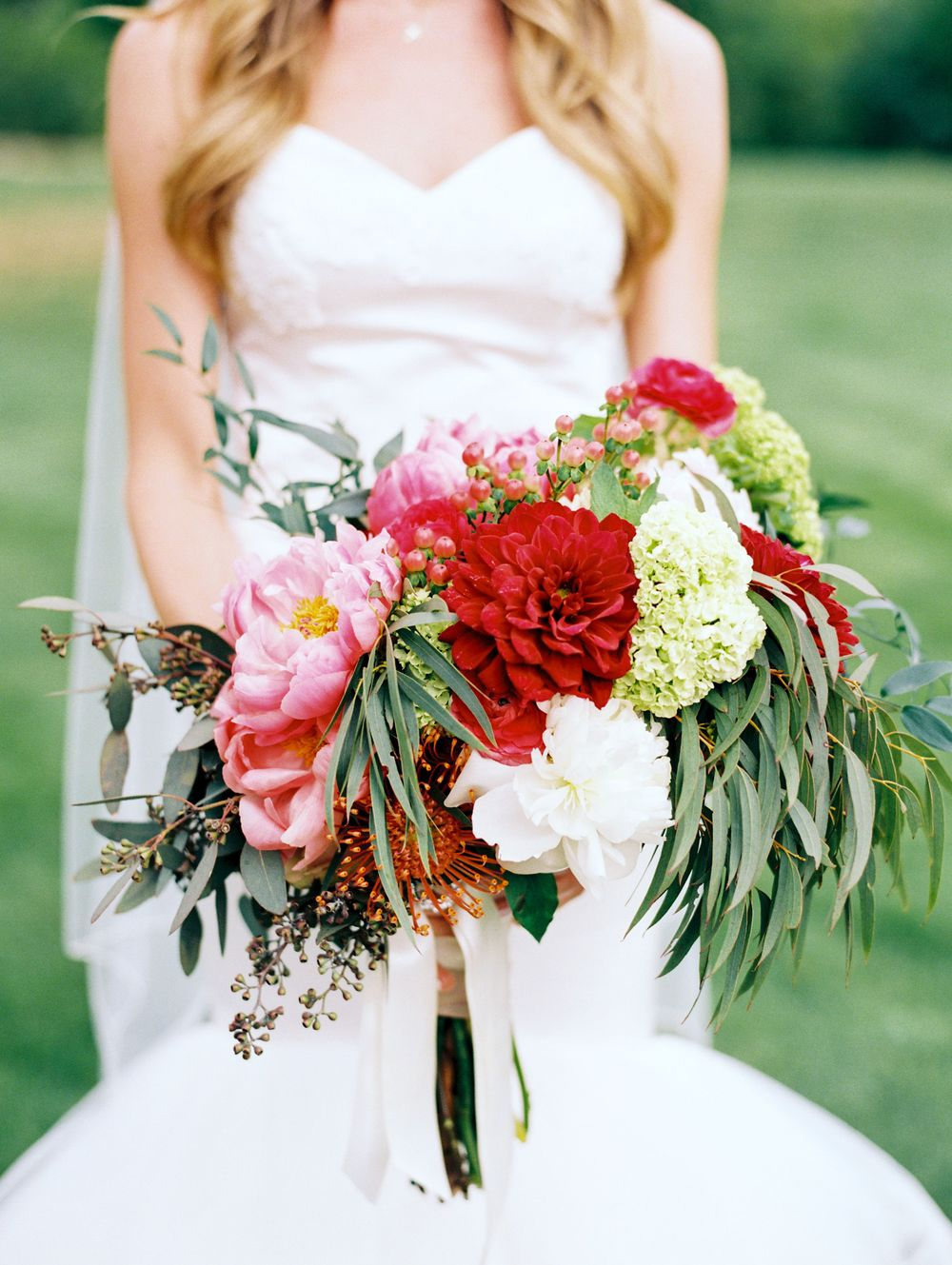 Fairie's Petticoat and Coral Charm Peonies, Red Dahlias, Orange Pin Cushion Protea, Coral Hypericum Berries, Red Ranunculus, Viburnum, Willow and Seeded Eucalyptus.